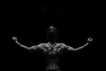 Fit woman demonstrate perfect back and shoulders on black background