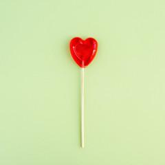 A Lollipop in shape of heart on green background