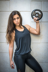 Portrait of beautiful slim young sportswoman holding weight plate against wall background.