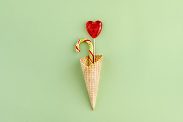 Lollipops in the shape of a tube and a heart in a waffle Cup on a green background