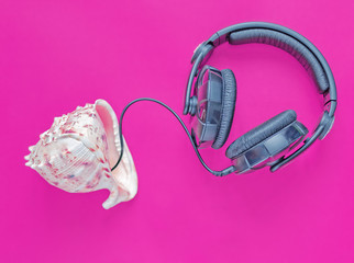 Large black headphones with leather ear pads are pressed on the seashell. Pink or ultraviolet background. Image on the theme of travel, rest, vacation, fun, music and parties