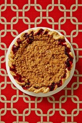Top view fruit pie with crumble topping on patterned background