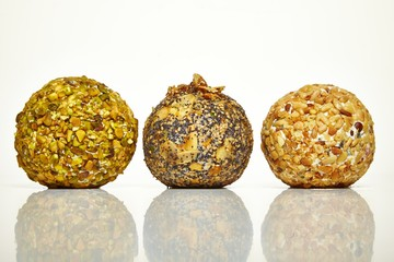 Three cheese balls coated with nuts on white background