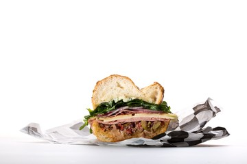 Half sandwich in paper wrapper on white background