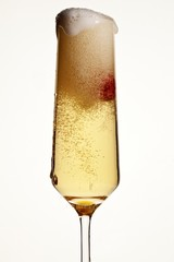 Low angle foamy overflowing champagne flute on white background