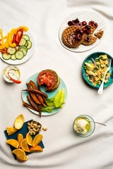 Plates with burger, pasta, waffles, fruit and vegetable slices, nuts and ice cream on white linen tablecloth