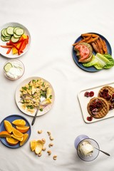 Plates with pasta, burger, waffles, fruit and vegetable slices, nuts and ice cream on white linen tablecloth