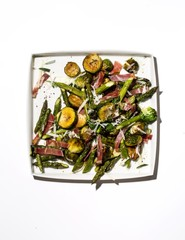 Plate of asparagus, Brussels sprouts and roasted vegetables on white background