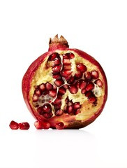 Cross section of red pomegranate with seeds on white background