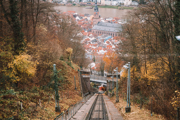 Railway road from the Heidelberg town up the hill. Classical cable car with train wagons near the old town in Germany during Autumn.