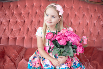 A little blond girl in colorful dress sits on big red sofa holding bunch of flowers