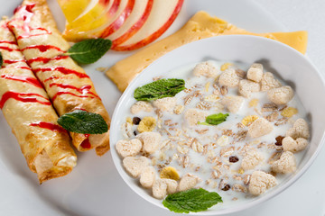 breakfast with pancakes, apples, cheese and musli with milk