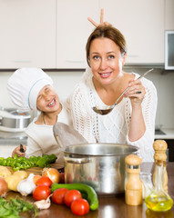mother and daughter preparing soup