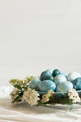 Naturally dyed Easter blue eggs, surrounded by white flowers.