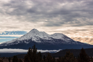 Mount Shasta in the clouds at sunset.