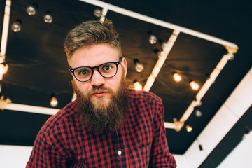 Portrait of cute hipster creative beard guy in glasses looking down into camera over black ceiling witn garland bulbs on background.