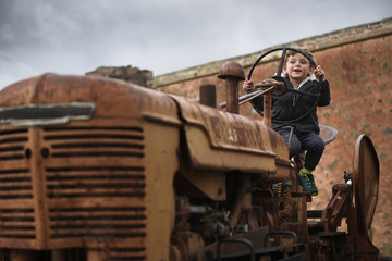 Boy playing sitting on old tractor at hacienda in Tepeapulco, Hidalgo, Mexico