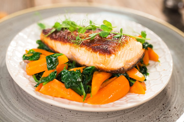 Salmon steak with carrot and spinach