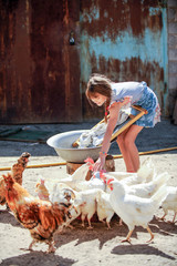 The farmer's daughter is washing his father's shirt in the yard