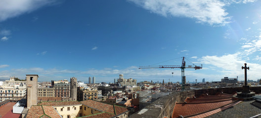 panoramic long image of the city of barcelona showing the roof of the old cathedral with the ancient and modern buildings and skyline extending to the horizon with towers and construction crane