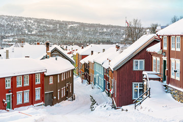 Colorful building facades at a street covered in snow during winter in the city of Roros