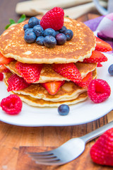 dish with pancakes and strawberry,raspberry and blueberry