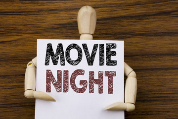 Conceptual hand writing text caption inspiration showing Movie Night. Business concept for Wathing Movies  written on sticky note paper on the wooden background. Holding by the sculpture.