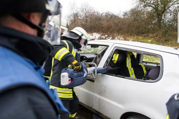 Feuerwehrmänner schneiden mit einer Rettungsschere ein Fahrzeug auf