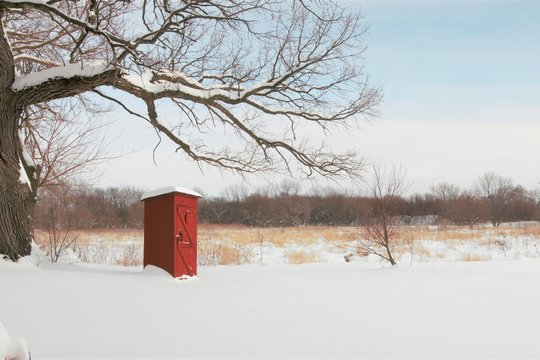 Winter scene of a red outhouse in a snowy field. Rural Midwest farm scene with a bright red outhouse. Concepts of winter, rustic, outdoors, cold