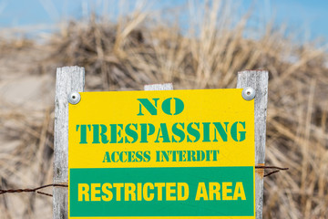 A no trespassing sign on the sand dunes of Maine's beach.