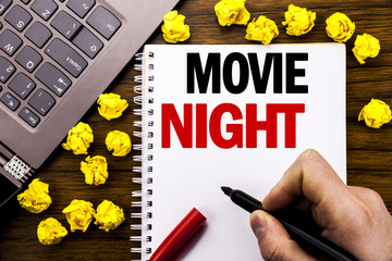 Conceptual hand writing text caption Movie Night. Business concept for Wathing Movies  Written on tablet laptop, wooden background with businessman hand, finger holding PC.