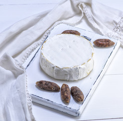 round Camembert cheese and pieces of smoked sausage