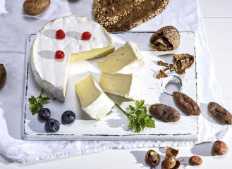 round Camembert cheese on a white wooden board