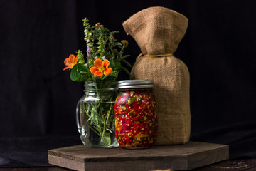 Still life with flowers and pickled peppers.