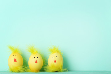 Yellow eggs with funny chicken faces on mint background