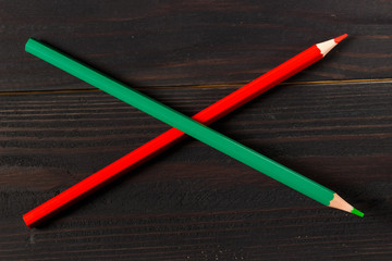 Red and green pencil on a dark background
