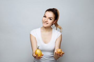 Healthy lifestyle. Studio shot on a white background of woman in sports clothing holding pear in one hand and cake in another. Sports girl trying to make decision between healthy and unhealthy food.
