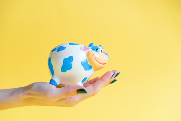 Treasure bank in a human hand on a yellow background. A woman's hand holds a piggy bank full of money.