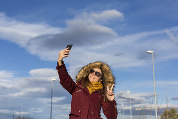 young beautiful happy woman taking a selfie with her mobile phone over blue sky background in the city. Autumn or winter season. Lifestyle