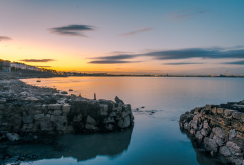 seascape on the east coast of Ireland during the sunset. sand rocks, low tide and colourful sky