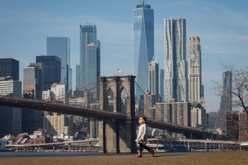 A girl walks through Brooklyn Bridge park with the Brooklyn Bridge and the lower Manhattan skyline in the distance during unseasonably warm weather in Brooklyn, New York