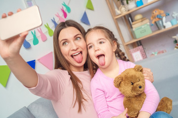 Mother and daughter together at home taking pictures on smartphone