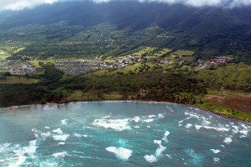 Aerial view of surf rolling across Kahului Bay beside the town of Kahului on the island of Maui, Hawaii, shot from a small, low-flying prop plane