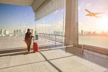 traveling woman with belonging luggage walking in airport terminal building and passenger plane flying over building in city