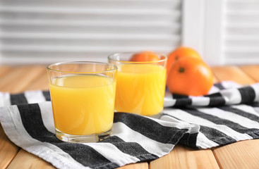 Glasses of fresh orange juice on wooden table