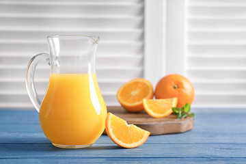 Glass jug of fresh orange juice with slice on wooden table