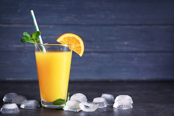 Glass of fresh orange juice with ice on table