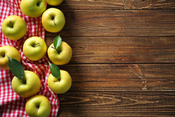 Ripe yellow apples on wooden background