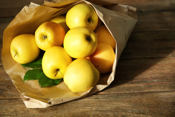 Paper package with ripe yellow apples on wooden background