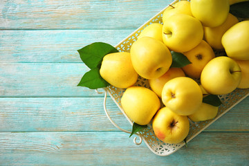 Tray with ripe yellow apples on wooden background